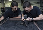 U.S. Navy Aviation Structural Mechanic 3rd Class Hunter McLane, right, and Aviation Structural Mechanic 3rd Class Carlos Gallardo measure a piece of steel for a brace in the airframe shop aboard the aircraft 130618-N-TX484-062.jpg