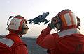 US Navy 030323-N-3181R-002 Members of the Crash and Salvage Crew aboard USS Bonhomme Richard (LHD 6) watch an AV-8B Harrier make a vertical landing on the flight deck.jpg
