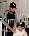 US Navy 051125-N-4124C-002 Information Systems Technician 2nd Class Brandon Kim, assigned to the amphibious transport dock USS Juneau (LPD 10), brings a smile to a patient at Sasebo's Sogo Hospital.jpg