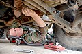 US Navy 060309-N-0553R-001 Construction Mechanic Sean Murphy, assigned to Naval Mobile Construction Battalion One (NMCB-1) reassembles a driveshaft on a High Mobility Multipurpose Wheeled Vehicle (HMMWV).jpg
