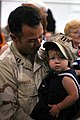 US Navy 070511-N-1688B-096 Lt. John Uyboco, an individual augmentee (IA) assigned to the 41st Brigade Combat Team in Afghanistan, holds his daughter in the Naval Station Norfolk MAC Air Terminal during a homecoming ceremony.jpg