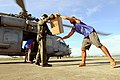 US Navy 080701-N-5961C-007 Aviation Warfare Systems Operator 2nd Class Slavek Glownia and a villager from Kalibo move a box of humanitarian supplies from an SH-60F Seahawk flown by members of Helicopter Anti-Submarine Squadron.jpg