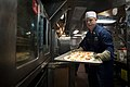 US Navy 100626-N-5319A-004 Chief Electronics Technician Daniel Kast assigned to Amphibious Squadron (PHIBRON) 5, loads a tray of pizzas into an oven.jpg