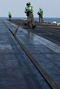 US Navy 120103-N-OY799-033 Aviation Boatswain's Mate (Equipment) Airman Miguel Bahena removes a catapult seal from catapult one on the flight deck.jpg