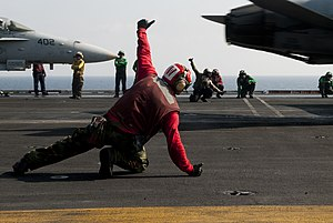 US Navy 120110-N-OY799-332 Aviation Ordnanceman 2nd Class Jason Ortiz signals safe to launch for an F-A-18C Hornet from Golden Dragons of Strike Fi.jpg