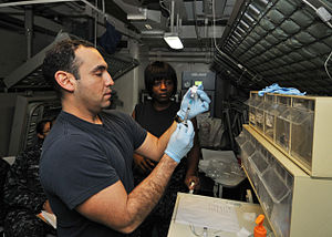 US Navy 120120-N-JO245-035 Hospital Corpsman 1st Class David Cano prepares a syringe with the anthrax vaccine for a Sailor aboard the Nimitz-class.jpg