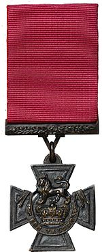 a bronze Cross pattée suspended from a crimson ribbon