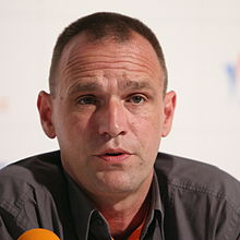 A middle-aged man with short black hair talking at a press conference.