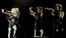 Madonna tanzt mit einer Gruppe von Tänzern in schwarzen Outfits