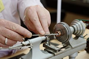 Watchmaker - A watchmaker's lathe in use to prepare a decorative watch component cut from copper.