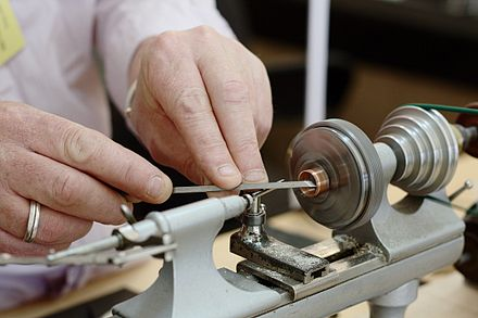 A watchmaker using a lathe to prepare a component cut from copper for a watch Watchmaker's Lathe in use.jpg