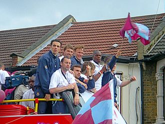 West Ham United F.C. - West Ham players on open-top bus near Upton Park celebrate winning the 2005 play-off final in Cardiff. From L-R Shaun Newton (crouching), Back row, Matthew Etherington, Jimmy Walker, Teddy Sheringham, Marlon Harewood, Front row Don Hutchison, Carl Fletcher, Elliott Ward and Mark Noble (with flag)