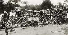 A group of around ten cyclists, climbing over a fence. Behind the fence are cars.