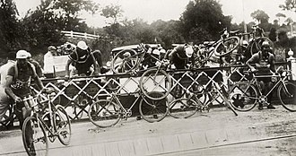 1932 Tour de France - Cyclists climbing the closed barrier of a railway crossing.