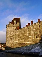 A photograph of a tall stone wall with a castle tower on the left, shining yellow from the low Sun. The tower and wall are pierced by small windows. the tower has a coned, red-tiled roof, with a clock built into one side. The sky behind the wall bue, with some clouds.