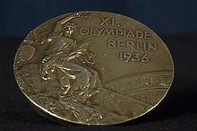 "A tarnished gold medal featuring a person in a toga, and the words ""XI Olympiade Berlin 1936""."