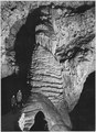 """Rock formation with women, dark background, 'The Rock of Ages, Big Room,' Carlsbad Caverns National Park,"" New Mexico. - NARA - 520023.tif"