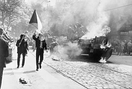 Un char d'assaut en feu au milieu de la chaussée entouré par plusieurs manifestants, dont l'un brandit un drapeau tchécoslovaque.