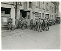 111-SC-329951 - Infantrymen of 1st U.S. Army gather in Bastogne, Belgium, to regroup after being cut away from their regiment by Germans in the enemy drive in this area. 110 Regt, 28th LNE Div FUSA Bastogne, Belgium.jpg