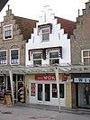 foto van Huis met gepleisterde trapgevel, bekroond door overhoekse pinakel. De treden afgedekt met natuurstenen platen. Puibalk