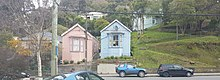 Two almost identical small wooden houses next to each. A pink one and a blue grey one. Set up from the street with a concrete retaining wall. A steep grassy bank is to the right. Parked cars and street posts in the foreground.