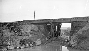 a black and white photograph of a railway bridge on an embankment