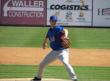 "A man in gray pants and a blue baseball jersey with ""METS"" on the chest prepares to pitch a baseball with his right hand."