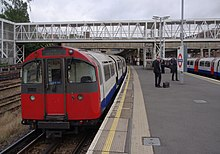 A westbound Piccadilly Line train, formed of 1973 stock, stands at Acton Town tube station with a service for Northfields.