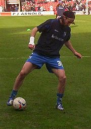 A man wearing a black t-shirt and blue shorts standing on a grass pitch, with a spherical football ball next to one of his feet.