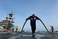 Airman David Saili moves a hose across the flight deck of the aircraft carrier USS George H.W. Bush (CVN 77) as the ship operates in the Atlantic Ocean on Dec 121202-N-TB177-393.jpg