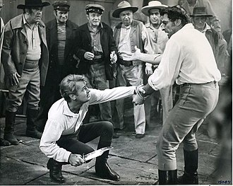 "The Iron Mistress - Jim Bowie played by Alan Ladd (on the left) in a knife dueling scene with the villain, ""Bloody Jack"" Sturdivant portrayed by American actor, Tony Caruso in the 1952 film,  The Iron Mistress."