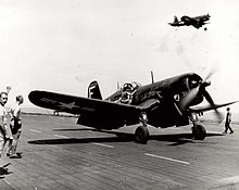 A Corsair on deck. A man stands nearby with fist upraised, giving a signal. There is another Corsair in the air above.