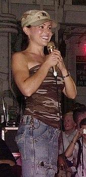 Milano speaking to sailors on USS Nimitz in 2003