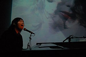 Antony Hegarty in 2008, at a grand piano singing into a microphone, in a black suit with her hair lank, against a projected-visual backdrop.
