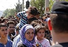 Plusieurs demandeurs d'asiles avec en premier plan une femme et des enfants.