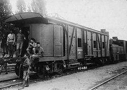 Approximately 4 soldiers, some of whom are armed, posing in front of a heavily armoured train car.