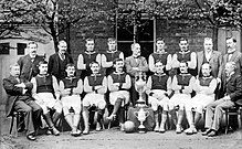 A group of men pose in two lines, one standing and the other seated. Eleven of the men are wearing dark-coloured football shirts with lighter sleeves, white shorts, shin pads and football boots. The remainder of the men are wearing formal suits. Almost all of the men sport moustaches. Displayed in the centre of the group are two large trophies.