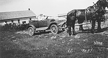 Two people in an automobile hitched to two horses