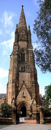 "The spire of St John's, as described in the text. The main door, off the street, opens into the base of the tower. The door is open and there is a sign saying ""Open church, all welcome to come in"""