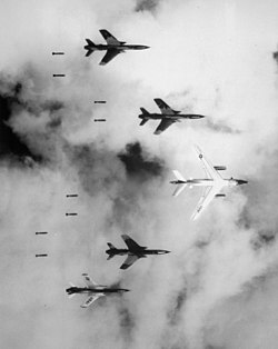 A U.S. EB-66 Destroyer and four F-105 Thunderchiefs dropping bombs on North Vietnam.