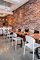 Brick wall white chairs and coffee cushions at Monki Inglewood.jpg
