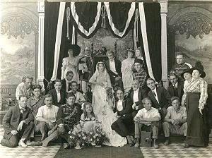 Francis Ford (actor) - Production still of the cast and crew of the Universal silent serial The Broken Coin (1915). Grace Cunard and Francis Ford are in the center on the throne, the young actress Gertrude Short is seated on the floor in front of Miss Cunard, and John Ford is third from the left. A Pathé motion picture camera is on the right in front the cameraman, most probably Harry McGuire Stanley.
