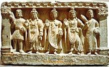 Steinstatuengruppe, eine buddhistische Triade, die von links nach rechts einen Kushan, den zukünftigen Buddha Maitreya, Gautama Buddha, den Bodhisattva Avalokiteśvara und einen buddhistischen Mönch darstellt.  2. - 3. Jahrhundert.  Guimet Museum