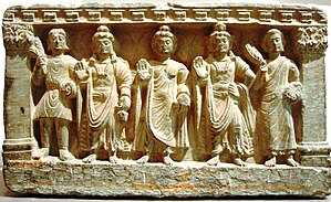 An early Mahayana Buddhist triad. From left to right, a Kushan devotee, the Bodhisattva Maitreya, the Buddha, the Bodhisattva Avalokitesvara, and a Buddhist monk. from the 2nd-3rd century AD