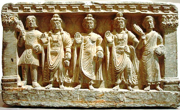 An early Mahayana Buddhist triad. From left to right, a Kushan devotee, the Bodhisattva Maitreya, the Buddha, the Bodhisattva Avalokitesvara, and a Buddhist monk. 2nd-3rd century AD, Gandhara.