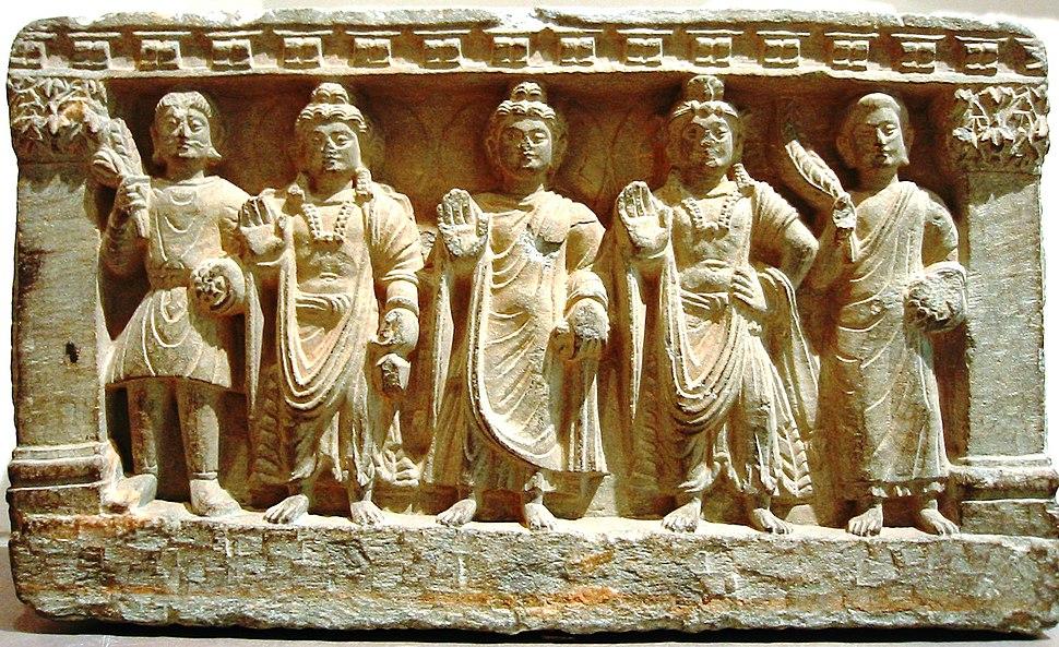 stone statue group, a Buddhist triad depicting, left to right, a Kushan, the future buddha Maitreya, Gautama Buddha, the bodhisattva Avalokiteśvara, and a Buddhist monk. 2nd—3rd century. Guimet Museum