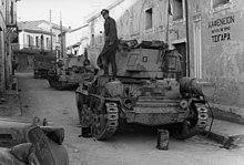 Deux blindés dans une rue, avec un officier allemand debout sur le premier de ceux-ci.