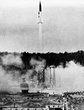 A black and white photograph showing the launch of a V-2 rocket; the rocket is twice its own height from the launchpad, which is partially obsured by clouds of smoke