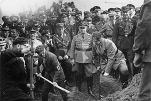 Reichsautobahn - Hitler shoveling dirt at the ceremonial inauguration of Reichsautobahn construction; behind him on the right Fritz Todt, on the left two workers helping him