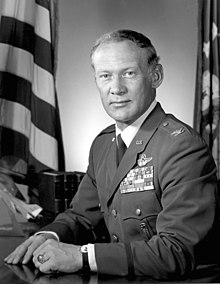 A black and white image of Aldrin in an air force colonel's uniform, with five rows of ribbons and astronaut wings. He wears his West Point class ring. He sits at a desk, with a flag him on both sides.